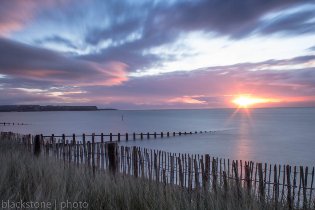 Sunrise over Dawlish Warren beach. Sand dunes in the foreground, sea and pink sunrise in the background.