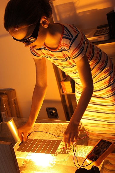 Child standing up and wearing goggles making solar panel artwork with small energy pack.