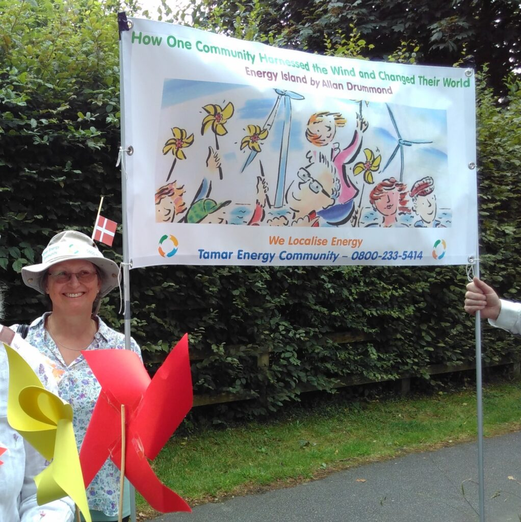 Woman smiling outside holding up a Tamar Community Energy Banner.