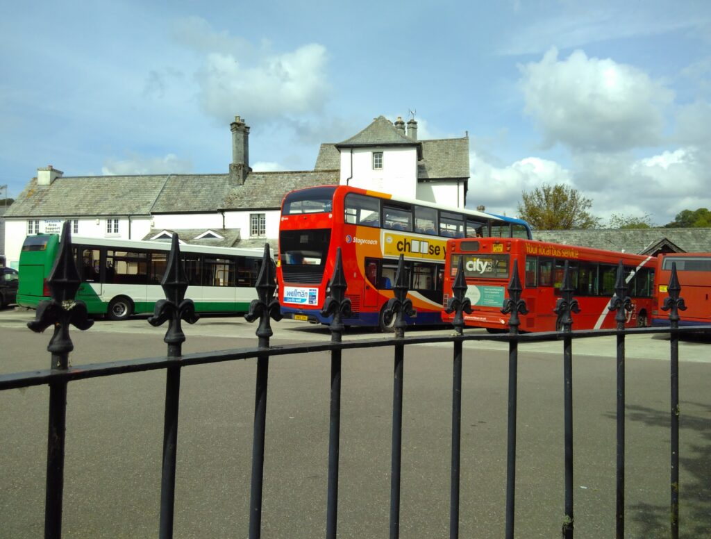 Tavistock Bus Station. 3 buses in distance of foreground.