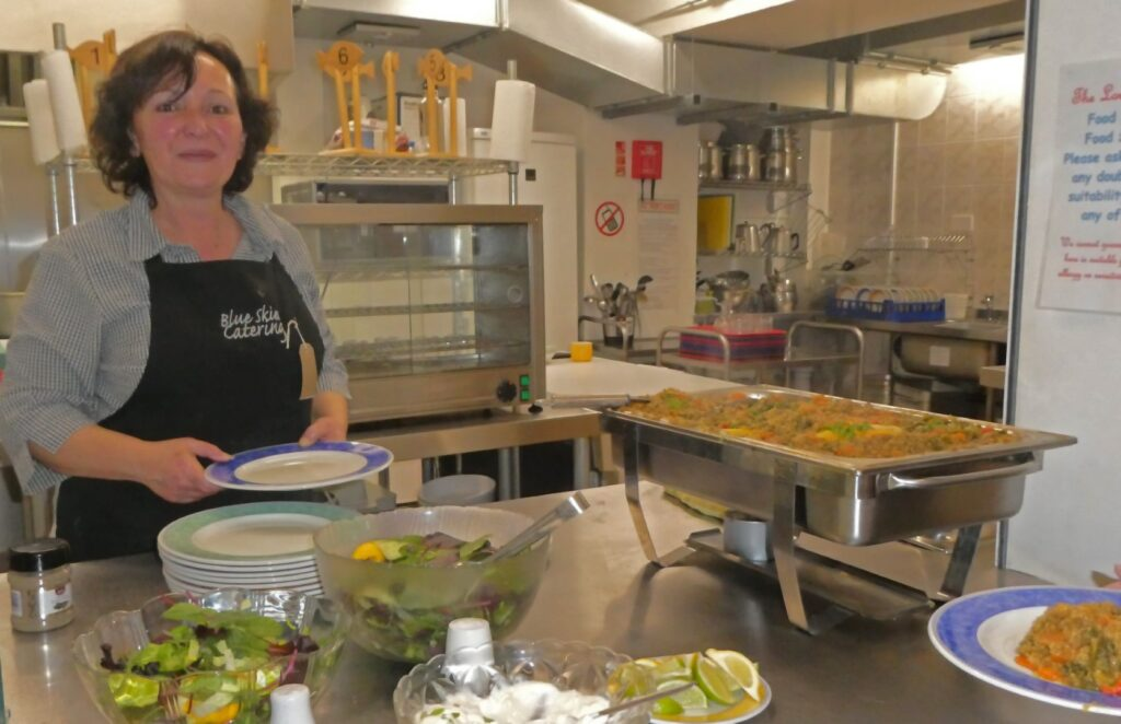 Woman in kitchen smiling whilst serving vegetarian stew at community hall.