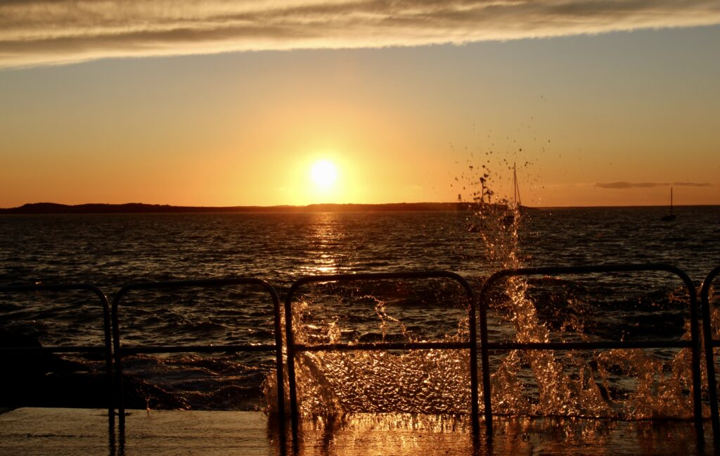 Sunset over the sea with waves splashing onto slipway in foreground.