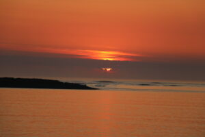 Sunset over the sea with an orange sky.