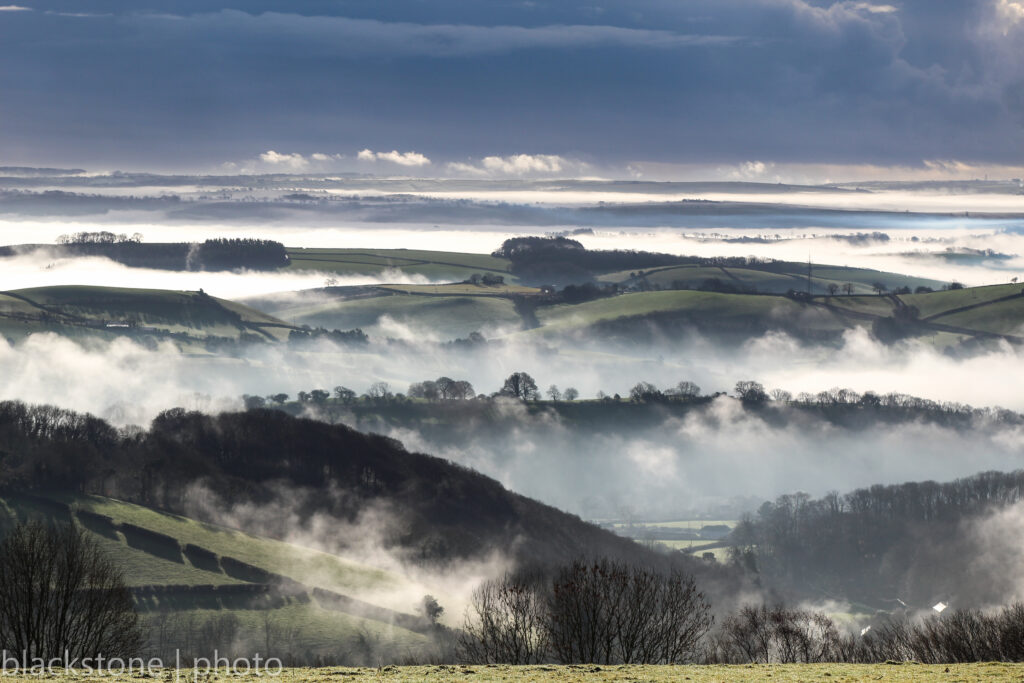 Mist in the valley over rolling green hills in South Dartmoor.