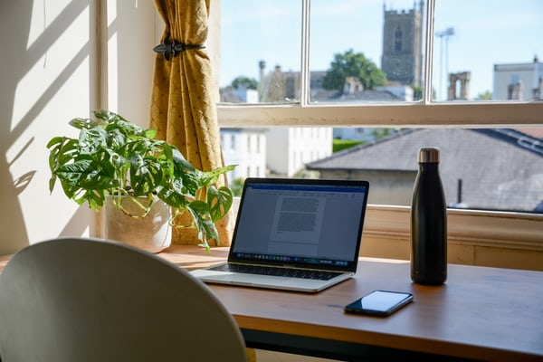 computer and water bottle on a desk in the sun